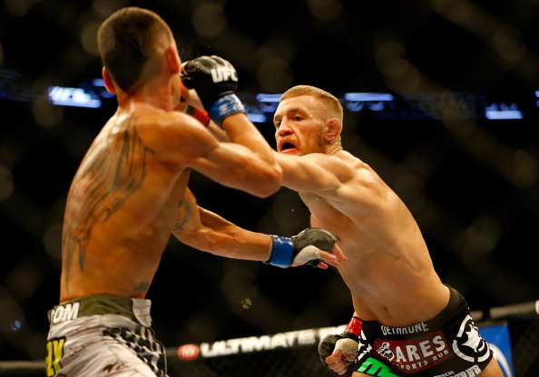 BOSTON, MA - AUGUST 17: Conor McGregor punches Max Holloway in their featherweight bout at TD Garden on August 17, 2013 in Boston, Massachusetts. (Photo by Jared Wickerham/Getty Images)