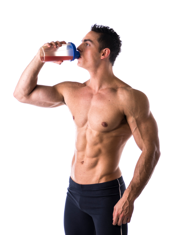 Muscular shirtless male bodybuilder drinking protein shake from blender. Isolated on white, looking at camera