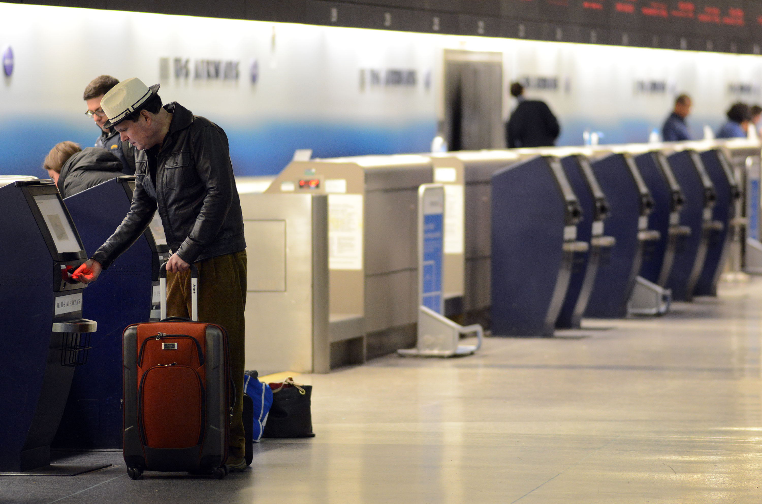 PHILADELPHIA, PA - NOVEMBER 26: Noel Grayson of Chesterbrook, Pennsylvania takes his boarding pass from a kiosk at Philadelphia International Airport November 26, 2014 in Philadelphia, Pennsylvania. Grayson was traveling to Asheville, North Carolina. A winter storm causes travel delays at the airport on the eve of Thanksgiving. (Photo by William Thomas Cain/Getty Images)