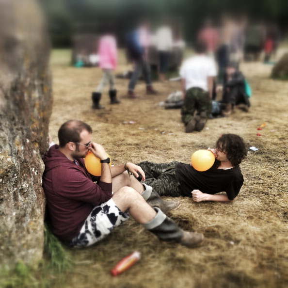 GLASTONBURY, ENGLAND - JUNE 27: (EDITOR'S NOTE: Image was created with an iPhone and processed using digital filters) People inhale nitrous oxide at the Stone Circle at the 2014 Glastonbury Festival at Worthy Farm on June 27, 2014 in Glastonbury, England. (Photo by Matt Cardy/Getty Images)