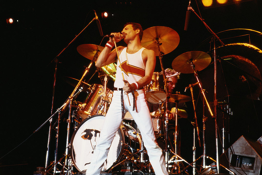 Freddie Mercury (1946-1991), singer with Queen, standing in front of a drumkit as he sings into a microphone on stage during a live concert performance by the band at the National Bowl in Milton Keynes, England, United Kingdom, on 5 June 1982. (Photo by Fox Photos/Hulton Archive/Getty Images)