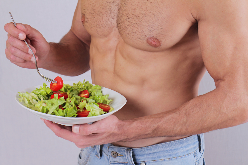 Close up of muscular man eating salad. Healthy life style, vegetarian bodybuilding concept.
