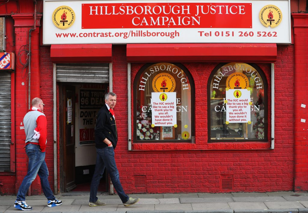 LIVERPOOL, UNITED KINGDOM - MAY 05: Fans walk past a Hillsborough Justice Campaign office prior to the UEFA Europa League semi final second leg match between Liverpool and Villarreal CF at Anfield on May 5, 2016 in Liverpool, England. (Photo by Richard Heathcote/Getty Images)