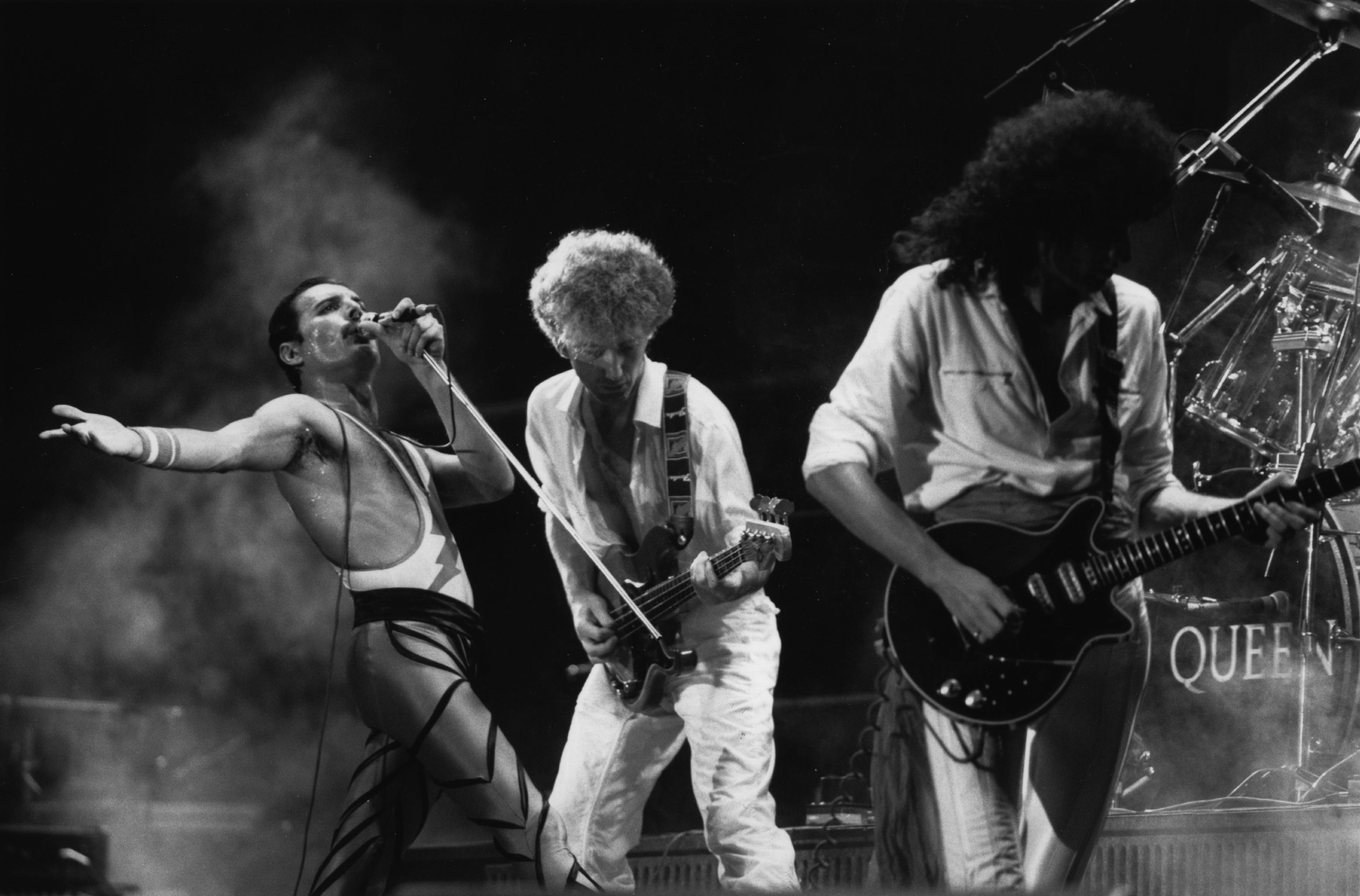 British rock group Queen in concert, from left to right; Freddie Mercury (Frederick Bulsara, 1946 - 1991), John Deacon, and Brian May. Original Publication: People Disc - HU0463 (Photo by Express Newspapers/Getty Images)
