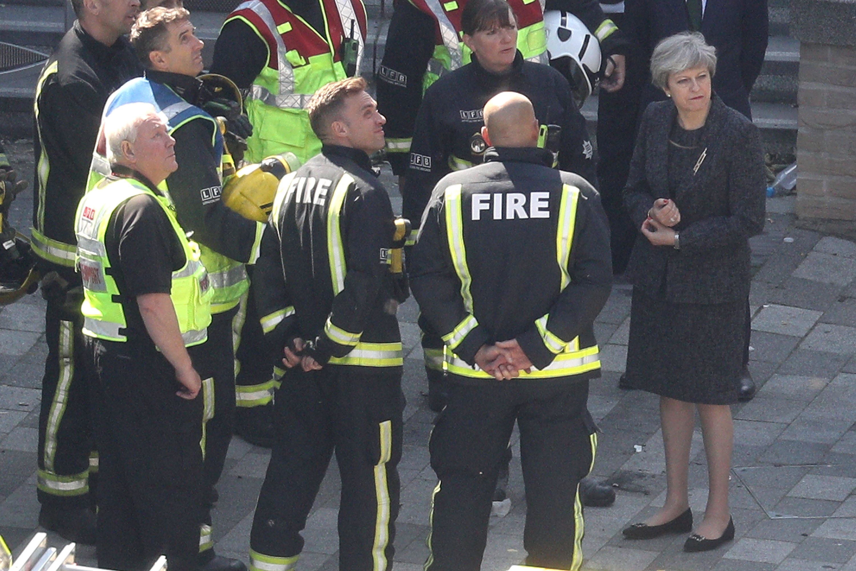 British PM May tries to quell public anger after deadly London fire