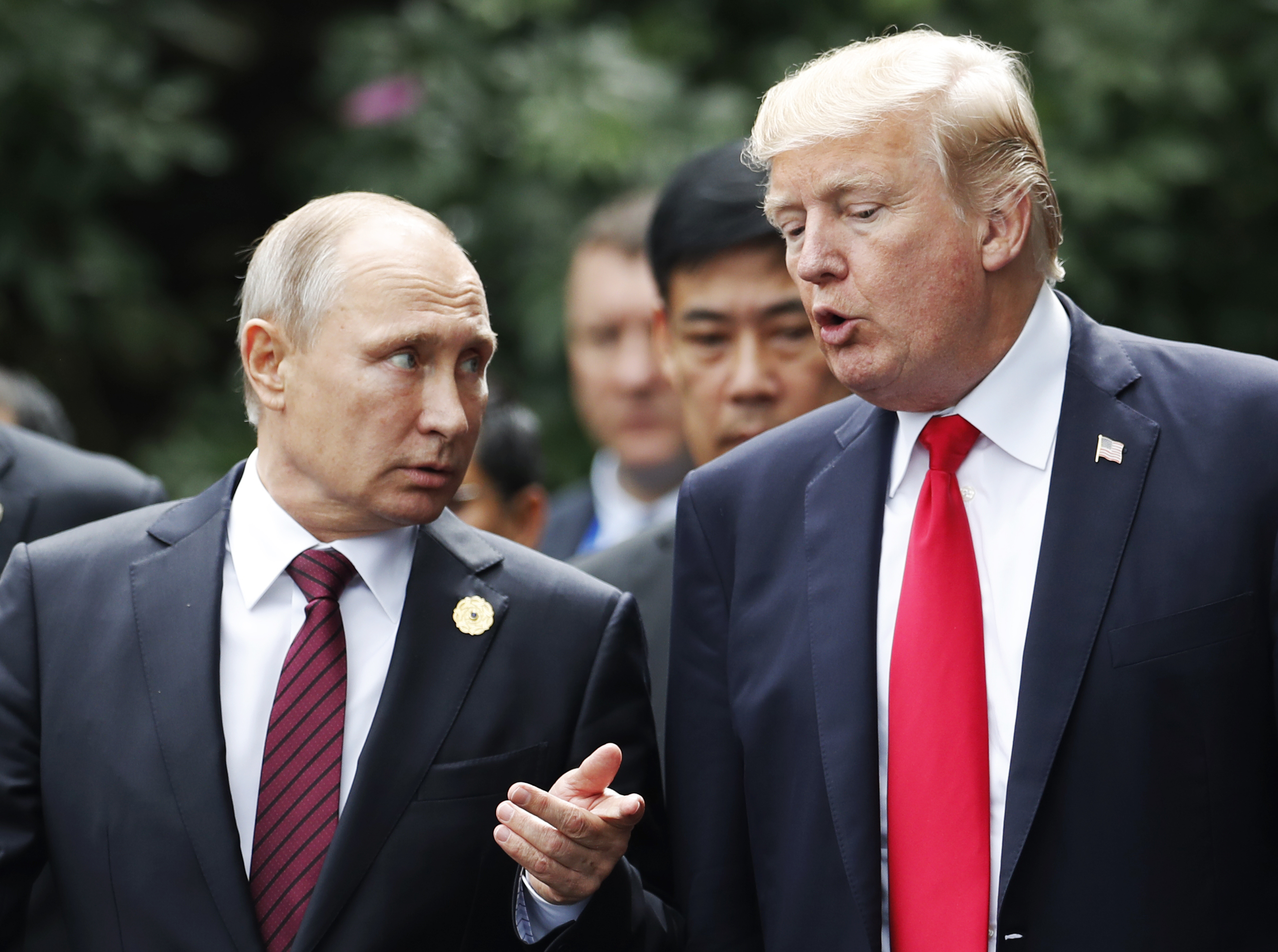"""US President Donald Trump (R) and Russia's President Vladimir Putin talk as they make their way to take the """"family photo"""" during the Asia-Pacific Economic Cooperation (APEC) leaders' summit in the central Vietnamese city of Danang on November 11, 2017. World leaders and senior business figures are gathering in the Vietnamese city of Danang this week for the annual 21-member APEC summit. / AFP PHOTO / POOL / JORGE SILVA (Photo credit should read JORGE SILVA/AFP/Getty Images)"""