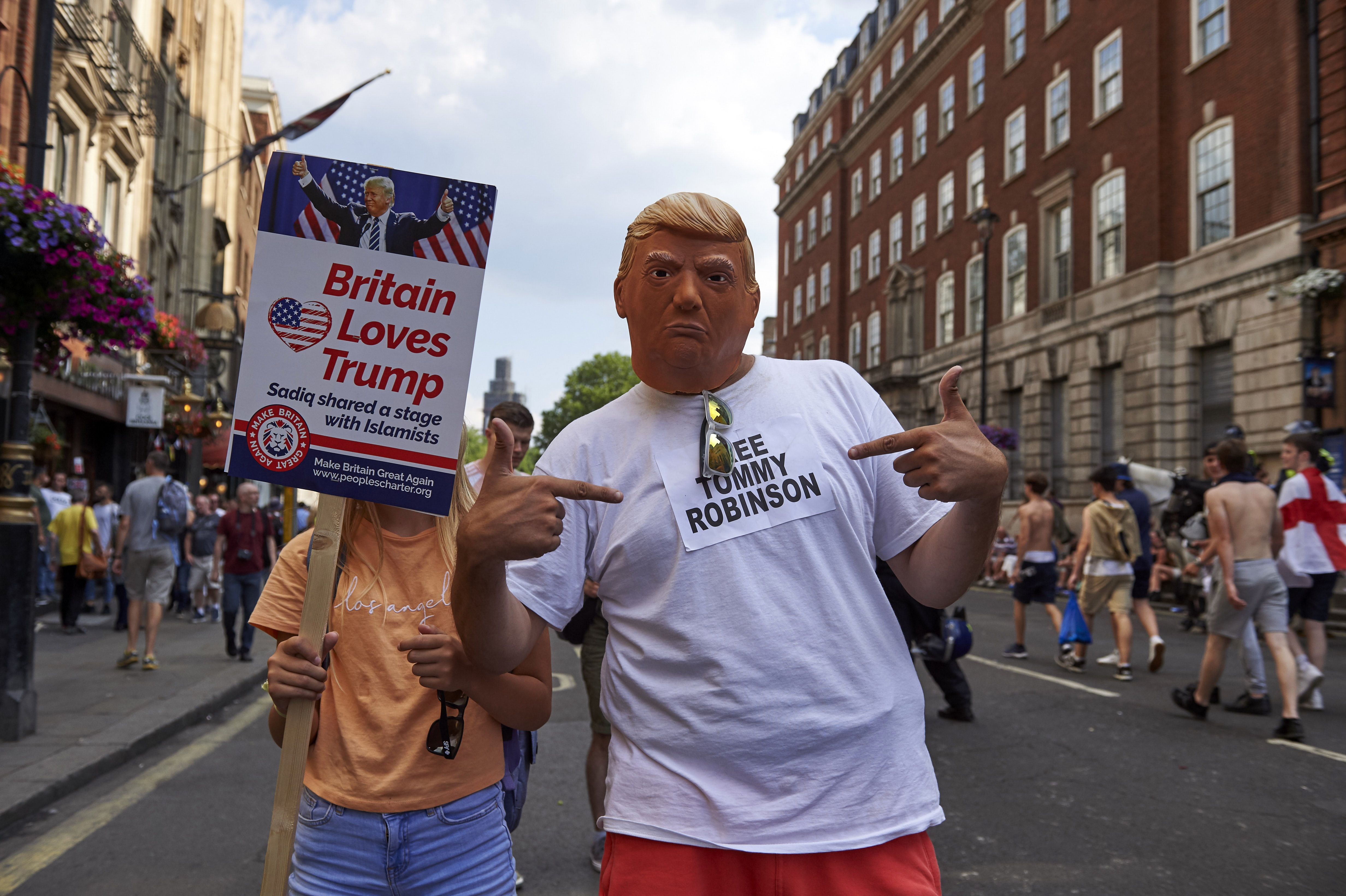 US President Donald Trump supporters pose for the camera as they mix with protesters at a rally by supporters of far-right spokesman Tommy Robinson in Trafalgar Square in central London on July 14, 2018, following the jailing of Tommy Robinson for contempt of court. (Photo by Niklas HALLE'N / AFP) (Photo credit should read NIKLAS HALLE'N/AFP/Getty Images)