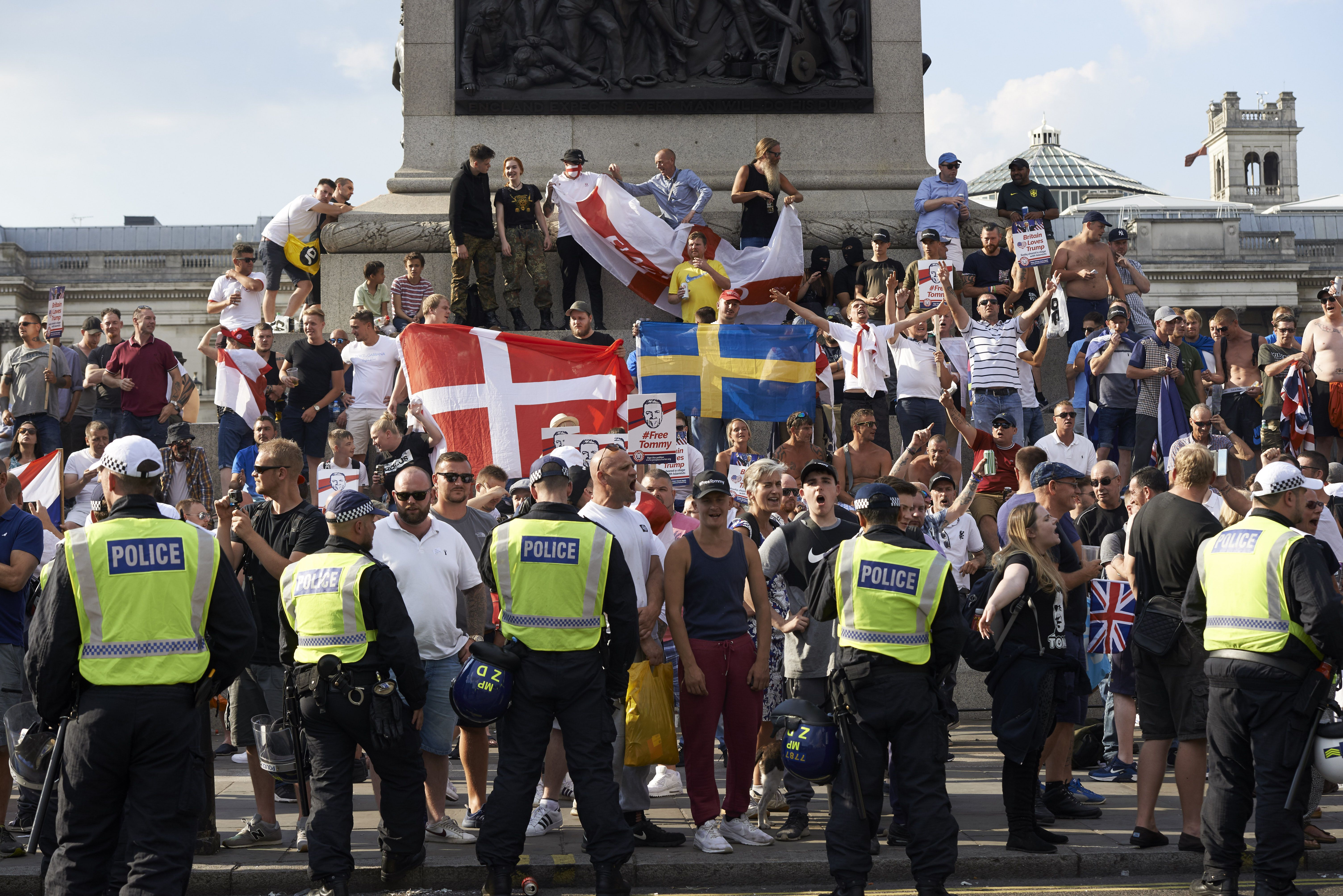 Protesters hold up flags and chant at a rally by supporters of far-right spokesman Tommy Robinson in Trafalgar Square in central London on July 14, 2018, following the jailing of Tommy Robinson for contempt of court. (Photo by Niklas HALLE'N / AFP) (Photo credit should read NIKLAS HALLE'N/AFP/Getty Images)