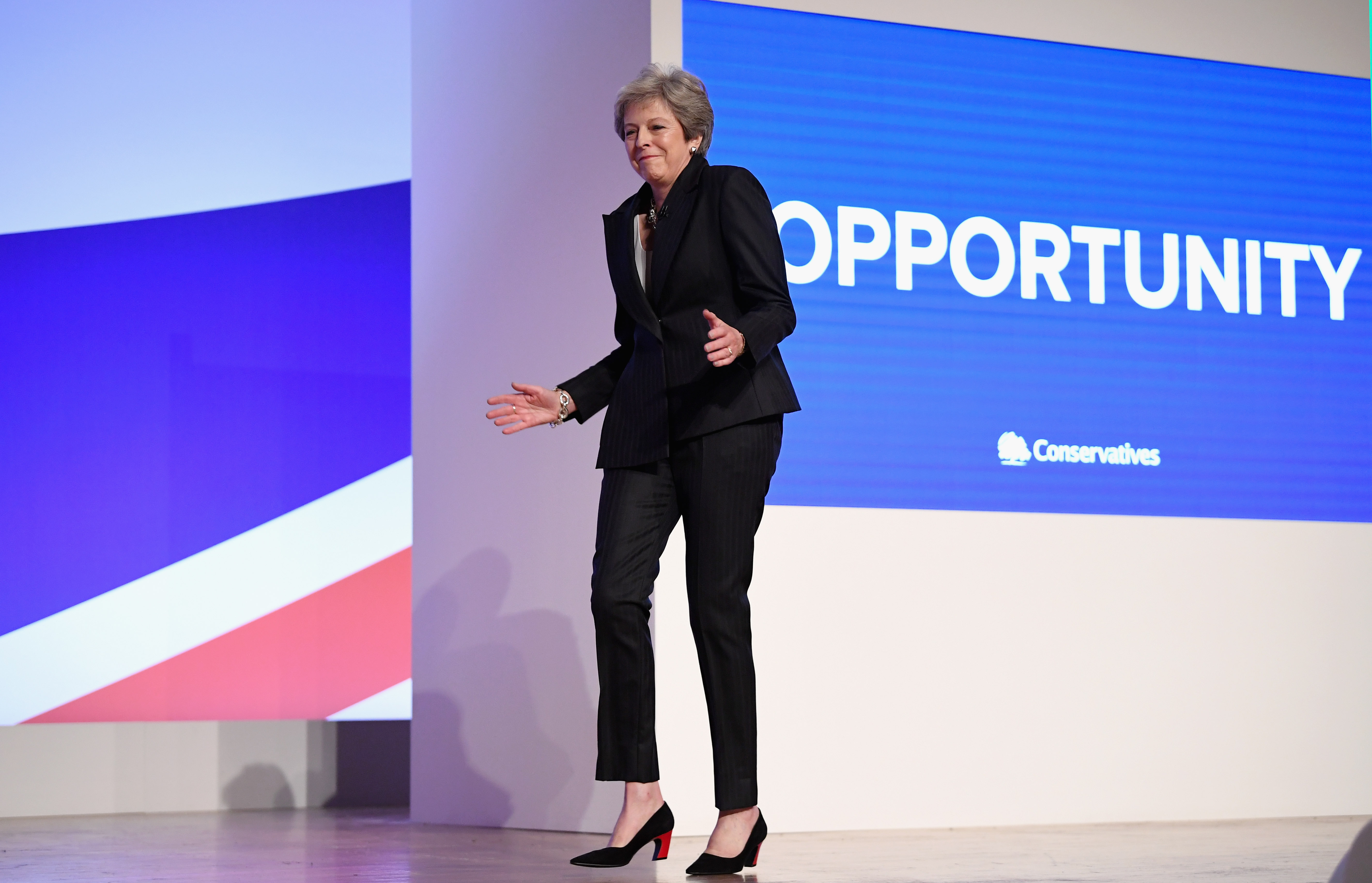 "BIRMINGHAM, ENGLAND - OCTOBER 03:  British Prime Minister Theresa May dances as she walks out onto the stage to deliver her leader's speech during the final day of the Conservative Party Conference at The International Convention Centre on October 3, 2018 in Birmingham, England. Theresa May delivered her leader's speech to the 2018 Conservative Party Conference today. Appealing to the ""decent, moderate and patriotic"", she stated that the Conservative Party is for everyone who is willing to ""work hard and do their best"". This year's conference took place six months before the UK is due to leave the European Union, with divisions on how Brexit should be implemented apparent throughout.  (Photo by Jeff J Mitchell/Getty Images)"