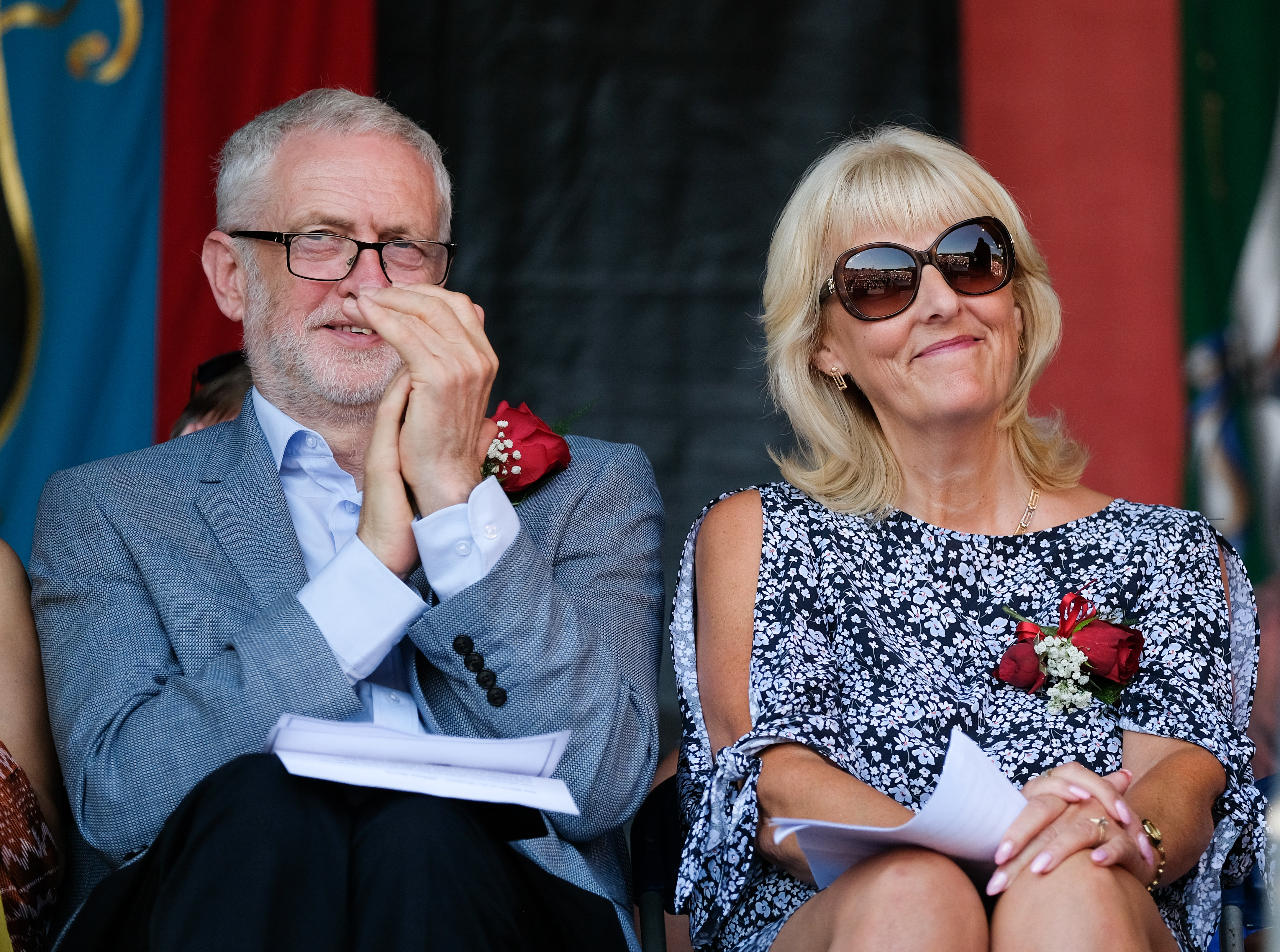 DURHAM, ENGLAND - JULY 14: Labour leader Jeremy Corbyn applauds as he sits with Labour General Secretary Jennie Formby and listens to speeches during the 134th Durham Miners' Gala on July 14, 2018 in Durham, England. Over two decades after the last pit closed in the Durham coalfield the Miners Gala or Big Meeting as it is known locally remains as popular as ever with over 200,000 people expected to attend this year. The gala forms part of the culture and heritage of the area and represents the communal values of the North East of England. The gala sees traditional colliery brass bands march through the city ahead of their respective pit banners before pausing to play outside the County Hotel building where union leaders, invited guests and dignitaries gather before then continuing to the racecourse area for a day of entertainment and speeches. Beginning in 1871 the gala is the biggest trade union event in Europe and is part of an annual celebration of socialism.  (Photo by Ian Forsyth/Getty Images)