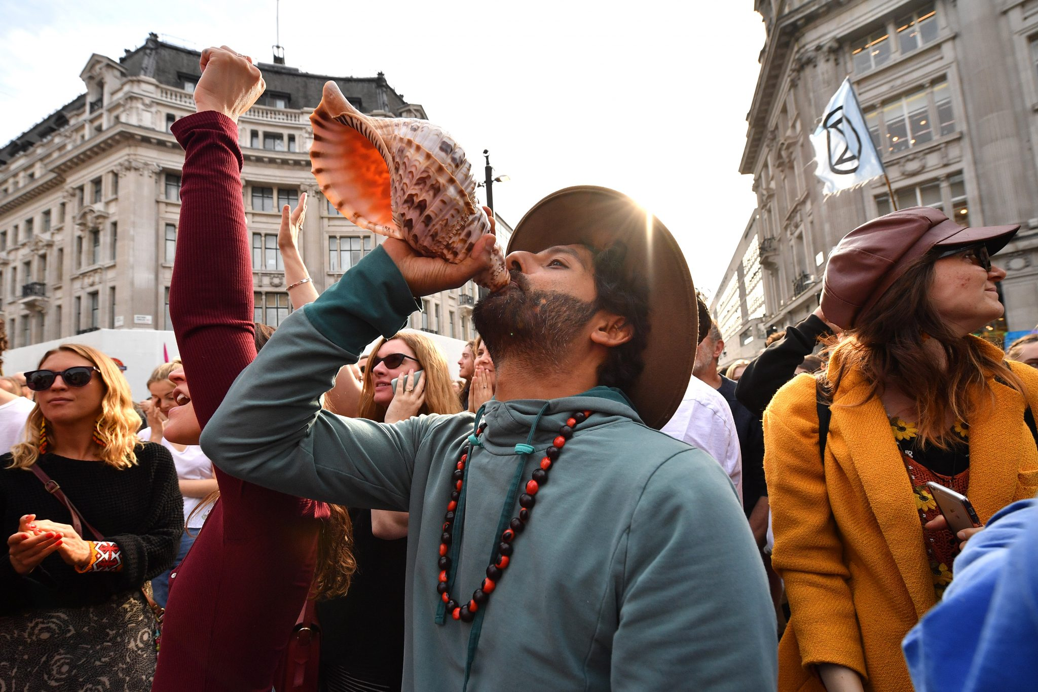A protester at the Extinction Rebellion demonstration in Oxford Circus sounds a conch (Credit: Leon Neal)