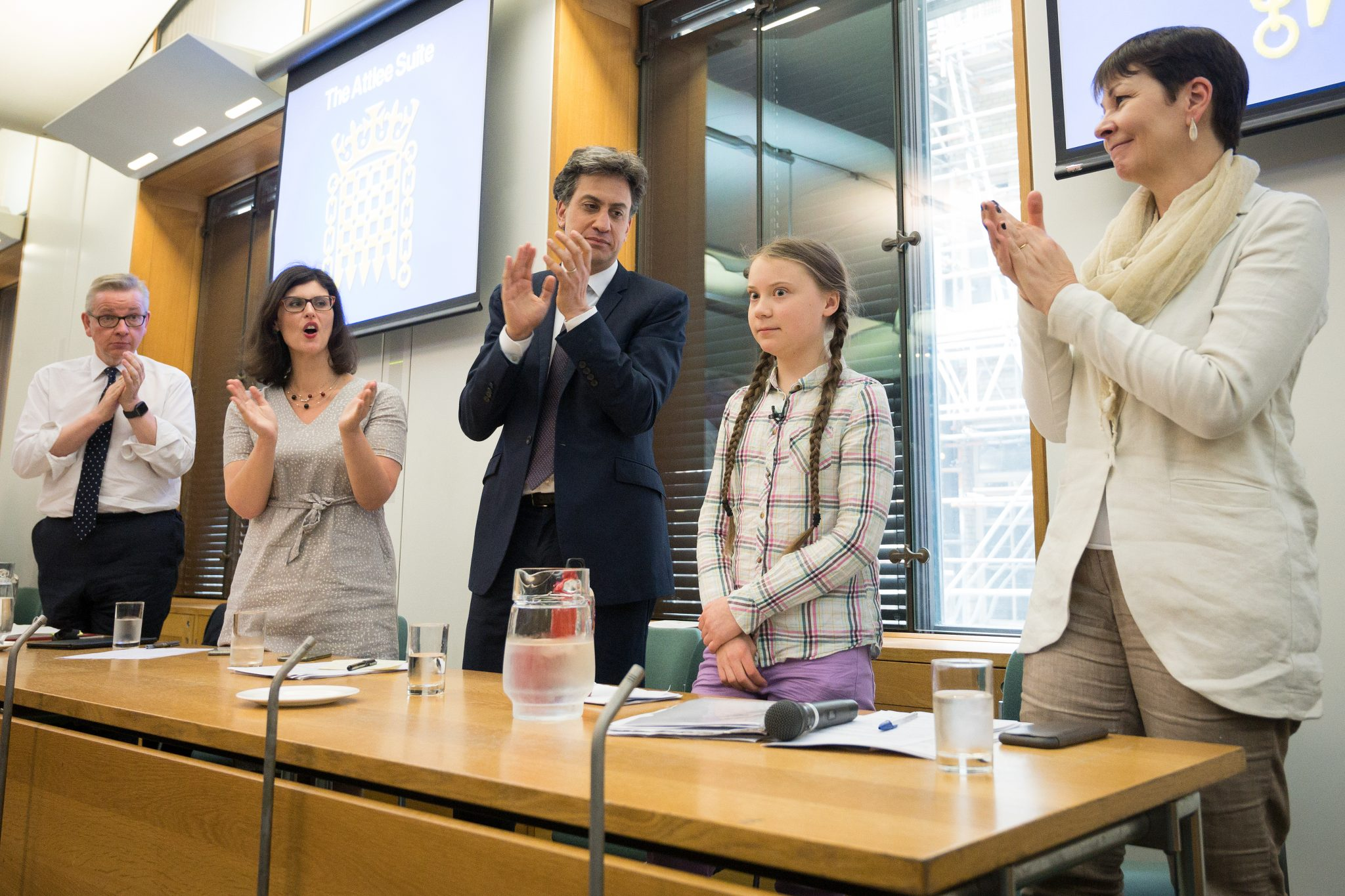 """Swedish environmental campaigner Greta Thunberg (2R) receives applause after addressing politicians, media and guests within the Houses of Parliament on April 23, 2019 in London, England. Her visit coincides with the ongoing """"Extinction Rebellion"""" protests across London, which have seen days of disruption to roads and transport systems, in a bid to highlight the dangers of climate change. (Photo by Leon Neal/Getty Images)"""
