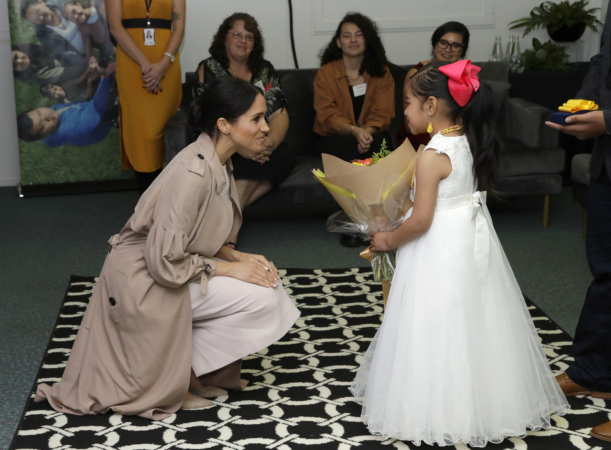 Meghan Markle with a child with flowers