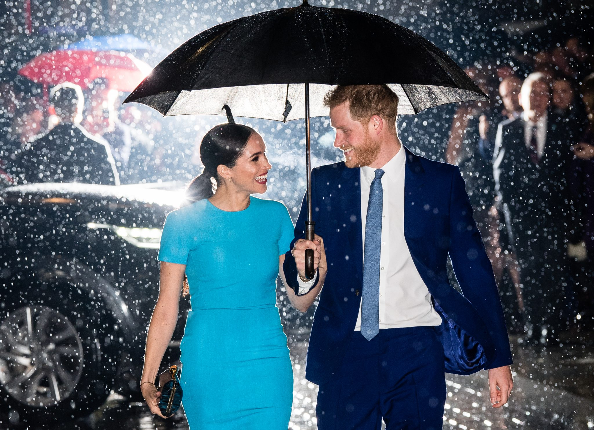 Harry and Meghan under an umbrella in the rain