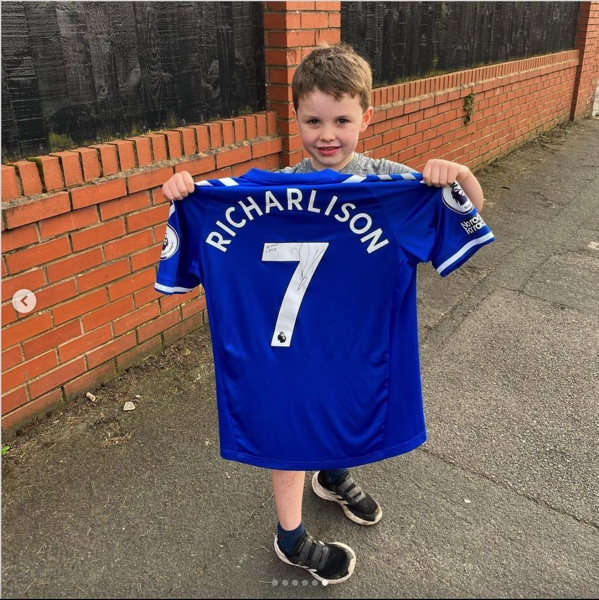 Young Everton fan with signed Richarlison shirt
