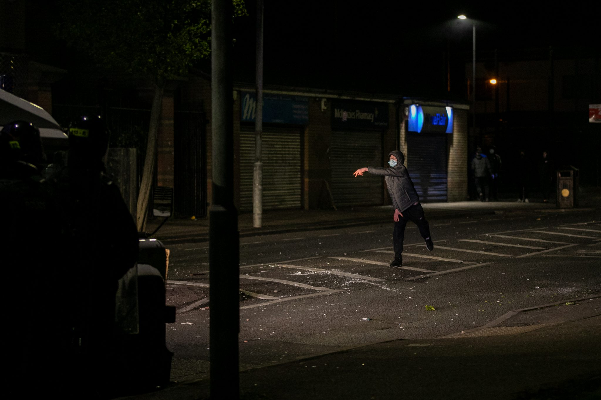 A hooded man throws an unseen item down the road toward police, he wears a medical face mask and the shops behind him are shuttered