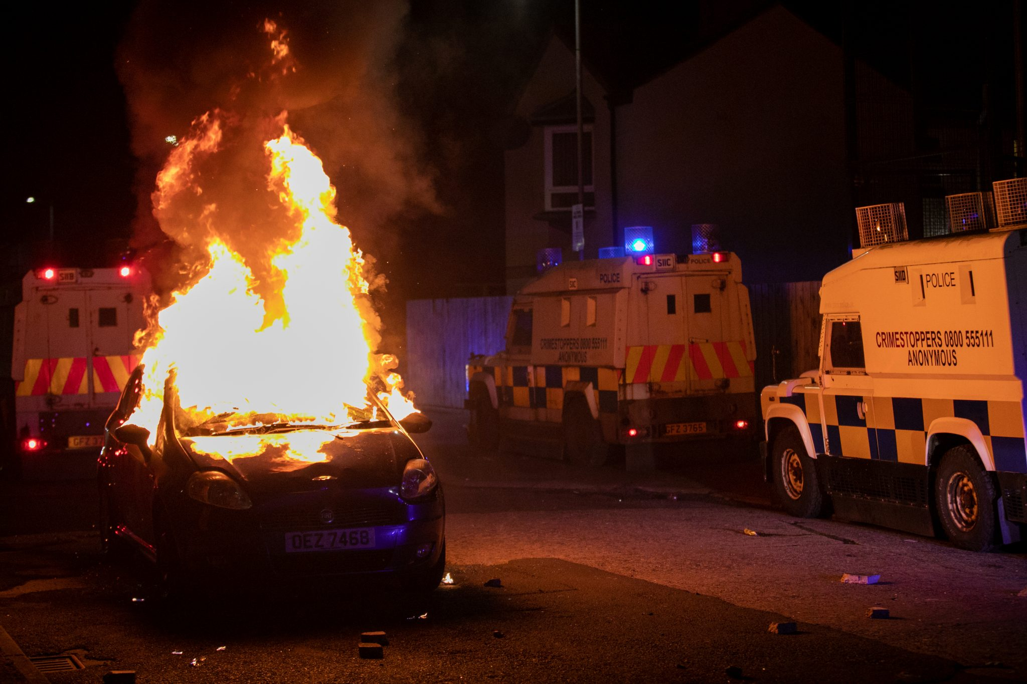 A car burns on the streets of Belfast, surrounded by police riot vans, at night in a residential area