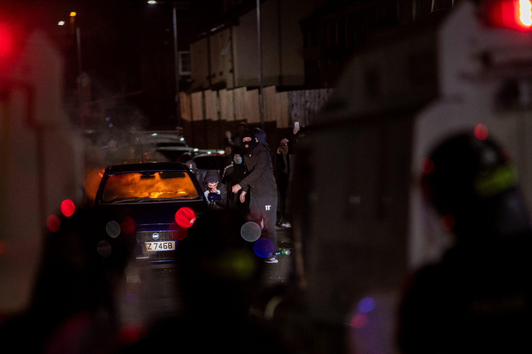 Men in balaclavas and tracksuits crouch don next to a burning car