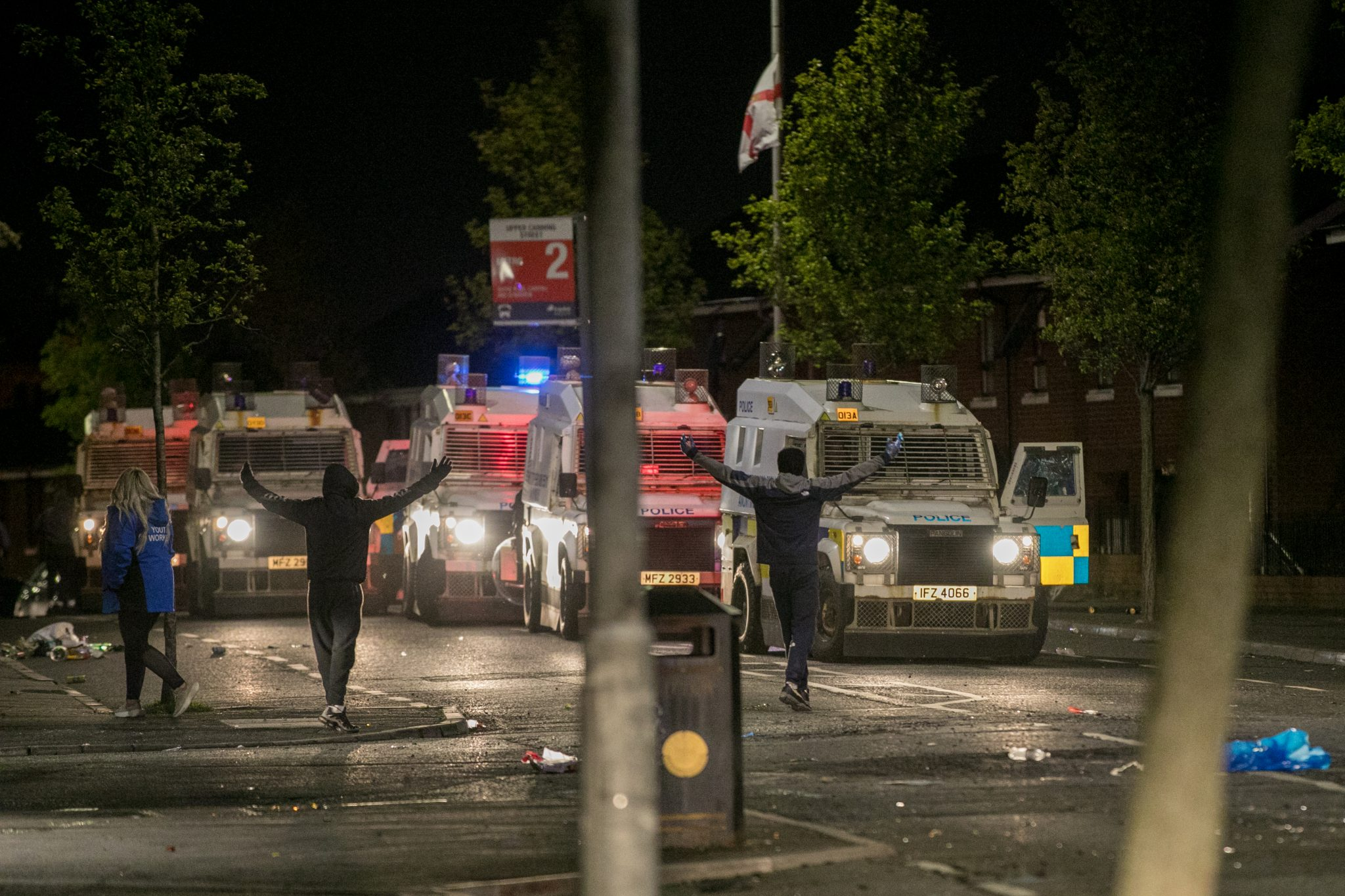 Two men taunt police officers in their riot vans, spreading their arms wide above their heads, a flag bearing the Red Hand of Ulster flies in the background
